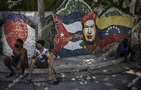 """People rest in front of artwork by Cuban artist José Antonio Rodríguez Fuster featuring the late Fidel Castro, left, and Hugo Chavez, right, and the Spanish phrase """"The best friend,"""" in the seaside village of Jaimanitas on the outskirts of Havana, Cuba, . This fishing town is popularly known as """"Fusterlandia"""" in honor of the painter and ceramicist"""