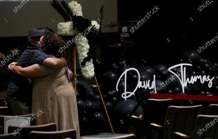 """LOS ANGELES, CA - APRIL 30, 2021 - - Nicky Bautista, left, and Michaela Pereira mourn the loss of their friend chef David Thomas at his memorial service inside the Holsinger Chapel at the Los Angeles Mission on April 30, 2021. Thomas, 61, who came up from the streets of Skid Row, eventually lead the kitchen as Food Service Director at the Los Angeles Mission over the past 20 years. """"The humility that matched his size,"""" said Pereira about her friend's formidable size. """"When you walked into that kitchen you were family,"""" she said. Thomas passed away earlier this month. """"The Mission has lost an indefatigable spirit, a fun-loving and caring soul, and the world has lost an amazing human being,"""" said Troy Vaughn, President and CEO of the Los Angeles Mission. Chef Michael Voltaggio, who spoke at the memorial, calculated that Chef Thomas was responsible for about 12 million meals for guests at the LA Mission. Only about 70 people were allowed to attend to maintain safety measures regarding COVID-19. (Genaro Molina / Los Angeles Times)"""