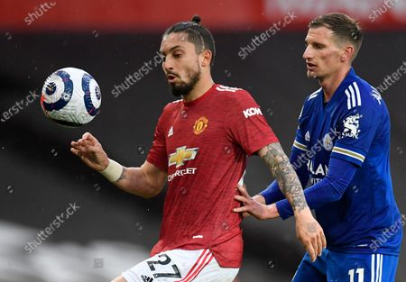 Manchester United's Alex Telles, left, duels for the ball with Leicester's Marc Albrighton during the English Premier League soccer match between Manchester United and Leicester City, at the Old Trafford stadium in Manchester, England