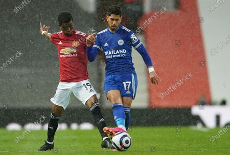 Manchester United's Amad Diallo, left, duels for the ball with Leicester's Marc Albrighton during the English Premier League soccer match between Manchester United and Leicester City, at the Old Trafford stadium in Manchester, England