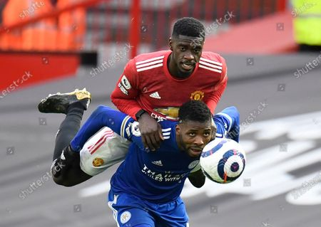 Manchester United's Axel Tuanzebe, top, duels for the ball with Leicester's Kelechi Iheanacho during the English Premier League soccer match between Manchester United and Leicester City, at the Old Trafford stadium in Manchester, England