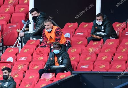 Manchester United's Harry Maguire, top left, looks out from the stands during the English Premier League soccer match between Manchester United and Leicester City, at the Old Trafford stadium in Manchester, England