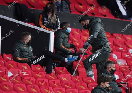 Manchester United's Harry Maguire, right, walks on the stands during the English Premier League soccer match between Manchester United and Leicester City, at the Old Trafford stadium in Manchester, England