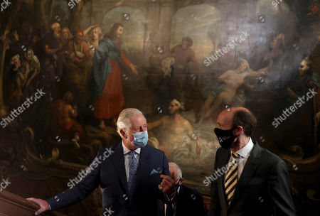 Prince Charles, Prince Charles speaks with Will Palin, chief executive of Bartâ??s Heritage during a visit to view St Bartholomew's Hospital North Wing, which includes the Great Hall and staircase which features paintings by artist William Hogarth on May 11, 2021 in London, England.