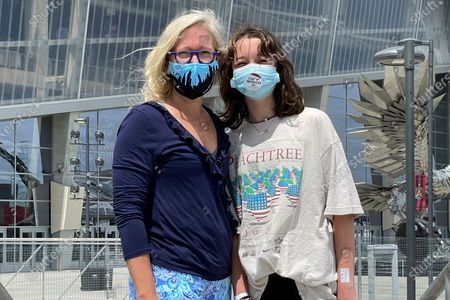 Stock Image of English Norman and her 12-year-old daughter, Jane Ellen Norman, pose for a photo outside Mercedes-Benz Stadium in Atlanta on . Jane Ellen and her 14-year-old brother Owen were vaccinated Tuesday morning, just after U.S. regulators expanded use of Pfizer's COVID-19 shot to those as young as 12