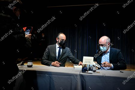 Le Havre Mayor and Former French prime minister Edouard Philippe flanked by his former counsellor and European deputy Gilles Boyer sign the book they write called Impressions and clear lines at the Mollat library.