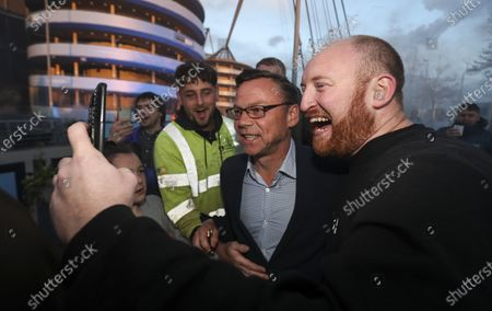 Paul Dickov arrives outside of the Etihad Stadium while fans celebrate after Manchester City win the Premier League title