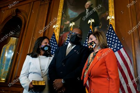 House Speaker Nancy Pelosi of Calif., right, poses for a photo during a ceremonial swearing-in for Rep. Troy Carter, D-La., center, as his wife Ana Carter, left, watches on Capitol Hill in Washington