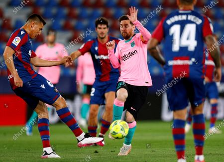 Stock Image of Levante UD's Oscar Duarte (L) in action against FC Barcelona's Leo Messi (R) during the Spanish LaLiga soccer match between Levante UD and FC Barcelona at Ciutat de Valencia stadium in Valencia, eastern Spain, 11 May 2021.