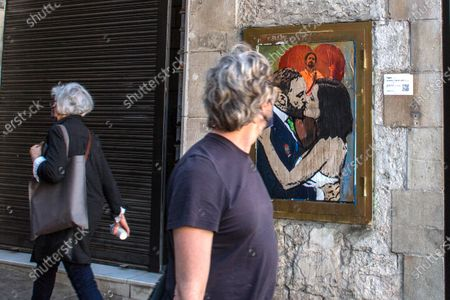 A man is seen looking at a new graffiti by artist TVBoy on a wall in Barcelona. A new graffiti signed by the artist TVBoy, depicting the result of the elections of the community of Madrid, held on May 4, 2021, where the re-elect president, Isabel Díaz Ayuso, is seen kissing Santiago Abascal, leader of the Spanish far right party Vox and a member of the Congress of Deputies in representation of Madrid, in front of Pablo Iglesias, former second Deputy Prime Minister of Spain and who was a candidate for the left-wing party, Podemos, leaving politics after the elections.