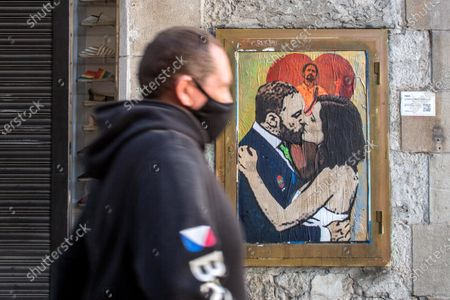 Stock Image of A man walks past a new graffiti by artist TVBoy on a wall in Barcelona. A new graffiti signed by the artist TVBoy, depicting the result of the elections of the community of Madrid, held on May 4, 2021, where the re-elect president, Isabel Díaz Ayuso, is seen kissing Santiago Abascal, leader of the Spanish far right party Vox and a member of the Congress of Deputies in representation of Madrid, in front of Pablo Iglesias, former second Deputy Prime Minister of Spain and who was a candidate for the left-wing party, Podemos, leaving politics after the elections.