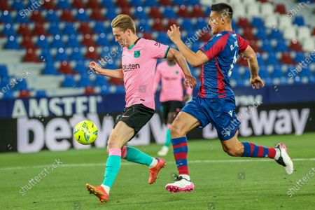 Levante's Oscar Duarte, right, vies for the ball with Barcelona's Frenkie de Jong during the Spanish La Liga soccer match between Levante and FC Barcelona at the Ciutat de Valencia stadium in Valencia, Spain