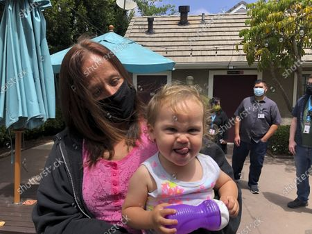 Lindsey Prescott looks at her 18-month-old daughter, Mia, as she giggles on in San Diego. Prescott moved into a converted San Diego hotel that Gov. Gavin Newsom visited Tuesday to announce a $12 billion program to get people like Prescott off the streets