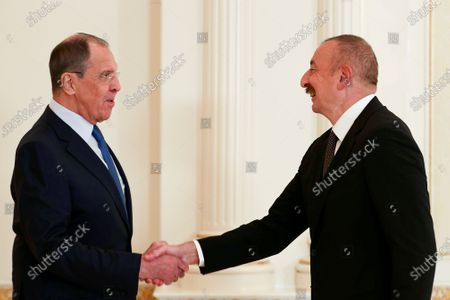In this handout photo released by Russian Foreign Ministry Press Service, Russian Foreign Minister Sergey Lavrov, left, shakes hands with Azerbaijani President Ilham Aliyev during his visit to Azerbaijan, in Baku, Azerbaijan