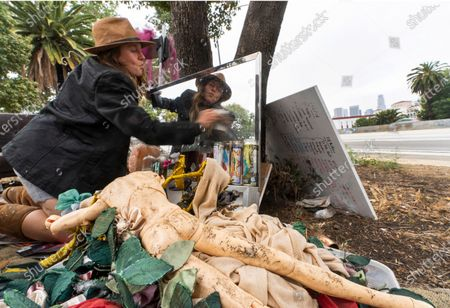 """Dawn Woodward, 39, who is homeless and originally from Arizona, dusts a mirror set outdoors in a homeless camp on the side of the CA-101 highway in the Echo Park neighborhood in Los Angeles . California Gov. Gavin Newsom on Tuesday proposed $12 billion in new funding to get more people experiencing homelessness in the state into housing and to """"functionally end family homelessness"""" within five years"""