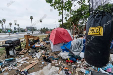 """Trashed punching bag is left at a homeless encampment is seen on the side of the CA-101 highway in Echo Park neighborhood in Los Angeles . California Gov. Gavin Newsom on Tuesday proposed $12 billion in new funding to get more people experiencing homelessness in the state into housing and to """"functionally end family homelessness"""" within five years"""