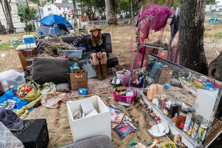 """Dawn Woodward, 39, who is homeless and originally from Arizona, sits outdoors in a homeless camp on the side of the CA-101 highway in Echo Park neighborhood in Los Angeles . California Gov. Gavin Newsom on Tuesday proposed $12 billion in new funding to get more people experiencing homelessness in the state into housing and to """"functionally end family homelessness"""" within five years"""