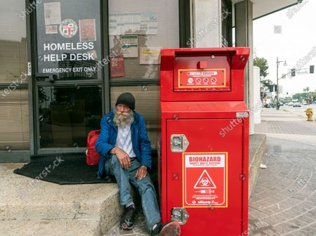 Homeless person Doug Lemaster, 68, originally from Montana, shelters next to the closed Homeless Help Desk kiosk across from City Hall downtown in Los Angeles . California Gov. Gavin Newsom is proposing $12 billion in new funding to get more people experiencing homelessness into housing