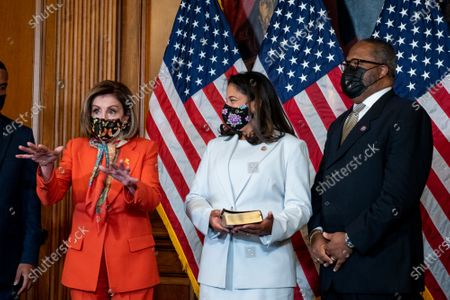 Speaker of the United States House of Representatives Nancy Pelosi (Democrat of California), left, holds a ceremonial swearing-in for United States Representative-elect Troy Carter (Democrat of Louisiana), right, as his wife Ana Carter, center, holds the Bible, at the US Capitol in Washington, DC,.