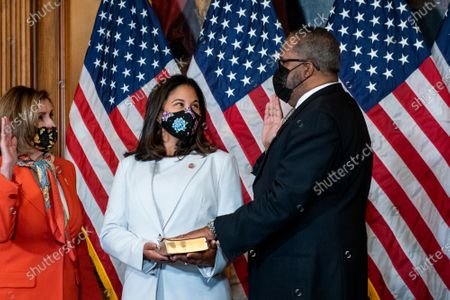 Stock Photo of Speaker of the United States House of Representatives Nancy Pelosi (Democrat of California), left, holds a ceremonial swearing-in for United States Representative-elect Troy Carter (Democrat of Louisiana), right, as his wife Ana Carter, center, holds the Bible, at the US Capitol in Washington, DC,.