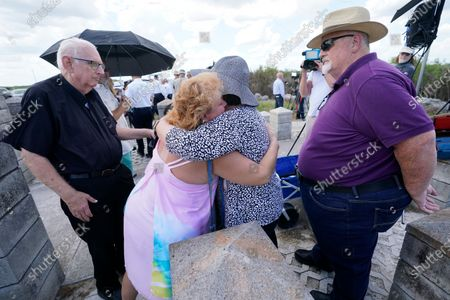 Stock Image of Christy Rivers, center left, and Jane Lathem, of Rome, Ga., hug as Lathems husband Warren, right, and Father David Smith, left, look on after a remembrance ceremony to commemorate the 25th anniversary of the ValuJet Flight 592 crash in 1996, on the edge of the Everglades in Miami. The Lathems lost their 20-year-old son Ray in the crash as he was returning from a church mission in Venezuela, Rivers worked for ValuJet fielding the calls from family members after the tragedy and Smith was a Chaplin at Jackson Memorial Hospital who was called in to comfort and help the families of the victims