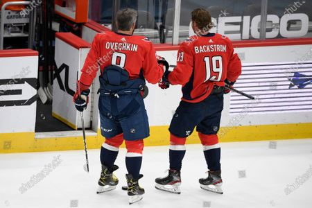 Washington Capitals left wing Alex Ovechkin (8) and center Nicklas Backstrom (19) leave the ice after they warmed up before an NHL hockey game against the Boston Bruins, in Washington