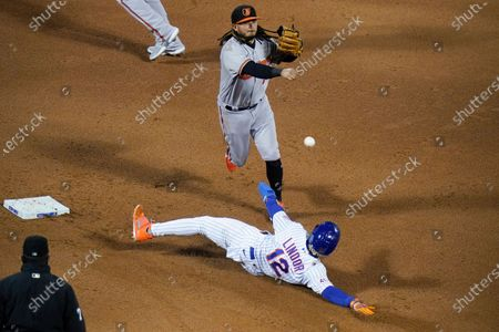 Baltimore Orioles' Freddy Galvis (2) throws to first base after forcing out New York Mets' Francisco Lindor (12) during the sixth inning of a baseball game, in New York. Michael Conforto was safe at first