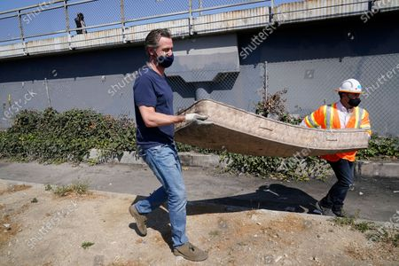 """California Gov. Gavin Newsom, left, carries an old mattress as he joins a cleanup effort, in Los Angeles. Newsom on Tuesday proposed $12 billion in new funding to get more people experiencing homelessness in the state into housing and to """"functionally end family homelessness"""" within five years"""