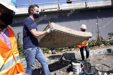 """California Gov. Gavin Newsom joins a cleanup effort, in Los Angeles. Newsom on Tuesday proposed $12 billion in new funding to get more people experiencing homelessness in the state into housing and to """"functionally end family homelessness"""" within five years"""