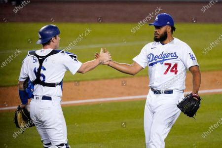 Stock Photo of Los Angeles Dodgers catcher Will Smith, left, and relief pitcher Kenley Jansen congratulate each other after the Dodgers defeated the Seattle Mariners 6-4 in an interleague baseball game, in Los Angeles