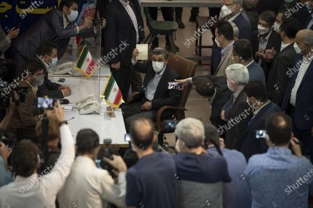 Former president Mahmoud Ahmadinejad (C) holds his Identification while attending the Iranian Interior Ministry building to register as a candidate for June 18, presidential elections, in central Tehran on May 12, 2021.