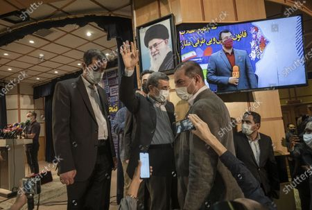 Former president Mahmoud Ahmadinejad (C) waves to media after reading his statement while leaving a press center after registering as a candidate for June 18, presidential elections, in the Iranian Interior Ministry building in central Tehran on May 12, 2021.