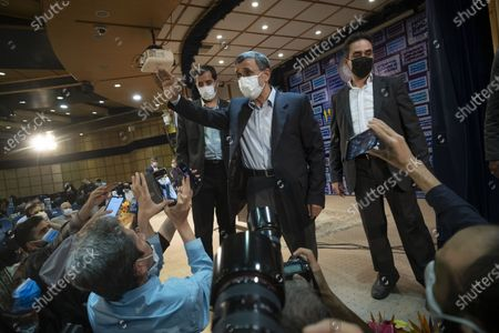 Former president Mahmoud Ahmadinejad (Top C) waves to media after reading his statement while leaving a press center after registering as a candidate for June 18, presidential elections, in the Iranian Interior Ministry building in central Tehran on May 12, 2021.