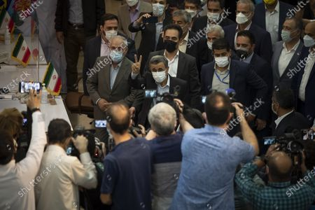 Former president Mahmoud Ahmadinejad (C) flashes a Victory sign while attending the Iranian Interior Ministry building to register as a candidate for June 18, presidential elections, in central Tehran on May 12, 2021.