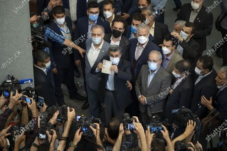 Former president Mahmoud Ahmadinejad (C) holds-up his Identification while attending the Iranian Interior Ministry building to register as a candidate for June 18, presidential elections, in central Tehran on May 12, 2021.