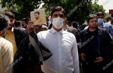 A supporter of former President Mahmoud Ahmadinejad holds his poster while Ahmadinejad registers his name as a candidate for the June 18, presidential elections at elections headquarters of the Interior Ministry