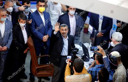 Former President Mahmoud Ahmadinejad waves to media while registering his name as a candidate for the June 18, presidential elections at elections headquarters of the Interior Ministry