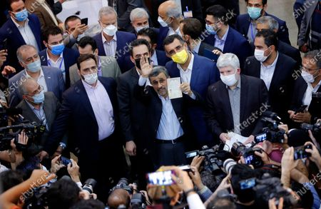 Stock Image of Former President Mahmoud Ahmadinejad waves to media as he shows his identification document while registering his name as a candidate for the June 18, presidential elections at elections headquarters of the Interior Ministry