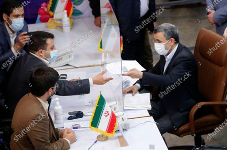 Former President Mahmoud Ahmadinejad, right, gives his identification documents to an elections headquarters staff while registering his name as a candidate for the June 18, presidential elections at the Interior Ministry