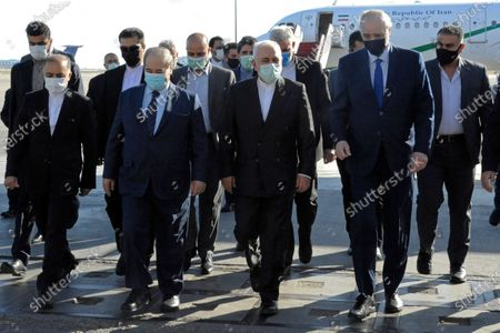 In this photo released by the Syrian official news agency SANA, Syria's Foreign Minister Faisal Mekdad, second left front, receives his Iranian counterpart Mohammad Javad Zarif, center, on his arrival to the airport, in Damascus, Syria, . Zarif said his country is ready for closer ties with its regional rival Saudi Arabia, saying Wednesday he hoped recent talks would lead to greater stability in the region