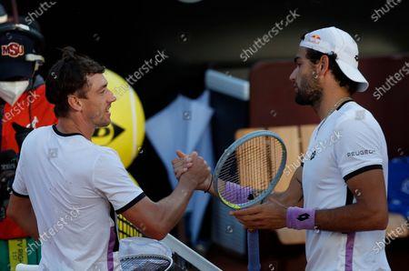 Stock Photo of Italy's Matteo Berrettini, right, shakes hands with Australia's John Millman at the Italian Open tennis tournament, in Rome, . Berrettini won 6-4, 6-2