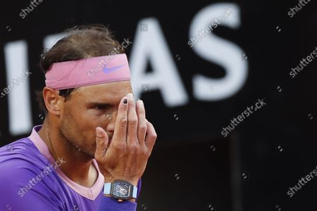 ISpain's Rafael Nadal touches his forehead during the match against Italy's Jannik Sinner returns the ball to at the Italian Open tennis tournament, in Rome