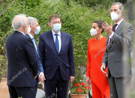 Spain's King Felipe VI (R) and Queen Letizia (2-R) chat with Valencia's regional President, Ximo Puig (3-R), Oliva's Mayor, David Gonzalez (2L), and Spanish Royal Academy's Director, Santiago Munoz Machado (L) upon their arrival at the home of poet Francisco Brines (unseen) in the town of Oliva, eastern Spain, 12 May 2021. The Spanish royal couple handed over 2020 Cervantes Prize to Spanish poet Francisco Brines in his home due to the delicate state of Brines' health amid coronavirus pandemic despite the awarding ceremony, traditionally held each 23 April in the town of Alcala de Henares.