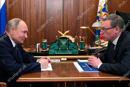 Russian President Vladimir Putin, left, listens to Omsk Region Governor Alexander Burkov during their meeting at the Kremlin in Moscow, Russia