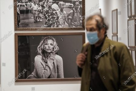 A visitor observes pictures at the exhibition 'Peter Lindbergh: untold stories', organized by the Kunstpalast in Düsseldorf in collaboration with the Peter Lindbergh Studio in Paris at the Artillery, in Turin, 12 May 2021. The exhibition runs from 13 May to 13 August 2021.