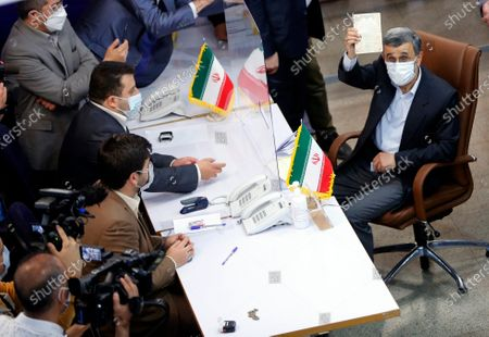 Former Iranian President Mahmoud Ahmadinejad shows his identification card to media while registering as a candidate for the June 18 Presidential election at elections headquarters of the interior ministry in Tehran, Iran.
