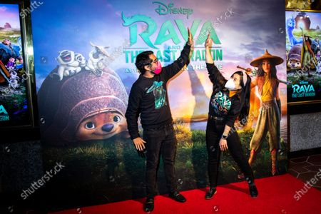 """Stock Photo of Carlos Lopez Estrada, one of the directors of """"Raya and the Last Dragon,"""" and actress Kelly Marie Tran, voice of """"Raya,"""" pose for photos at the entrance to El Capitan Theatre during the first Friday night of the re-opening of theaters in Los Angeles County."""
