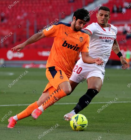 Sevilla's defender Diego Carlos (R) vies for the ball with Valencia's midfielder Goncalo Guedes (L) during the Spanish LaLiga soccer match between Sevilla FC and Valencia CF held at Sanchez Pizjuan stadium in Seville, southern Spain, 12 May 2021.