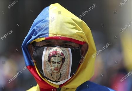 Protester, wearing a protective face mask designed with the face of Frida Kahlo, takes part in an anti-government protest in Bogota, Colombia, . The protests were sparked by a government proposed tax plan that was withdrawn on May 2 and the finance minister resigned the following day, but protests have continued across the country