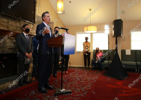 Governor Gavin Newsom speaks at a news conference about a $12 billion package bolstering the state's response to the homelessness crisis at the Kearney Vista Apartments, which houses homeless people in a converted hotel on Tuesday, May 11, 2021 in San Diego, CA. San Diego Mayor Todd Gloria, left, looks on.